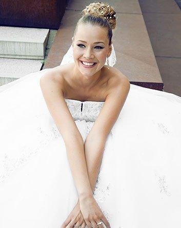 Blonde Braut glücklich im Brautkleid