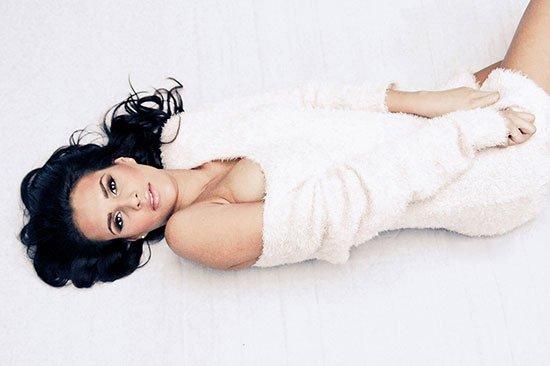 Junge Frau posiert nackt für Akt-Shooting in weißer Decke umhüllt