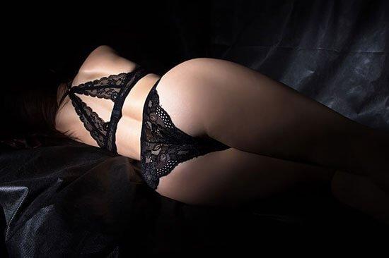 Akt Foto von Gesäß in sexy Dessous auf schwarzem Hintergrund