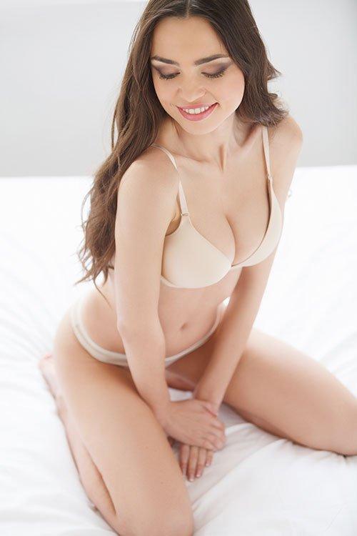 Frau in Unterwäsche lächelt schüchtern
